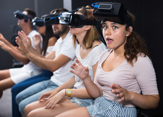 Portrait of frightened female after watching of exciting movie with VR glasses