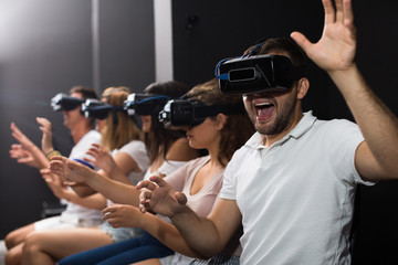 Portrait of young male which is watching exciting movie in VR glasses