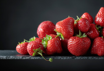 Ripe strawberries with green leaves on a black background.