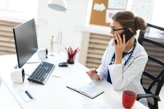 A young girl in a white robe is sitting at the desk in the office, talking on the phone and holding a pen in her hand. A stethoscope hangs around her neck.