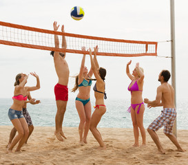 adults throwing ball over net and laughing