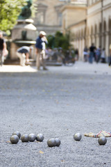 Some steel balls for petanque on crushed stones in the Hofgarten park in Munich, Germany. Unidentifiable blurred people in the background.