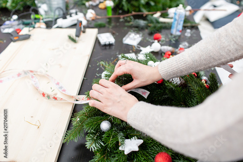 woman tying a bow ribbon decorated a christmas wreath attaches toys and decor with - How To Tie Decorative Bows For Christmas Decor