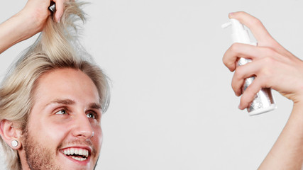Man applying spray cosmetic to his hair