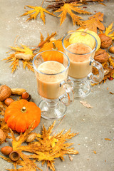 Pumpkin spice latte, hot coffee drink with whipped cream decorated with autumn leaves