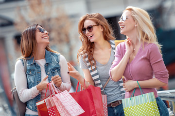 Happy surprised young women with shopping bags in the city Wall mural