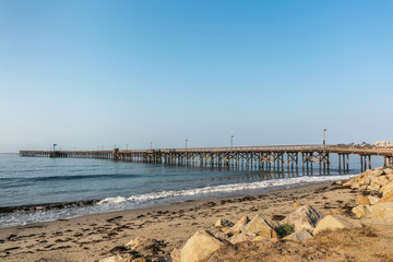 Goleta, California, USA - August 7, 2018: Long wooden pier stretches far into calm Pacific Ocean from right to left under blue sky. Sandy beach up front.