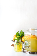 Summer healthy lemonade in big mason jar with lemon, orange and mint on white table. Copy space. Close up.