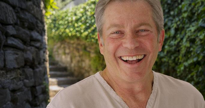 Happy mature Caucasian man smiles outside near stone staircase