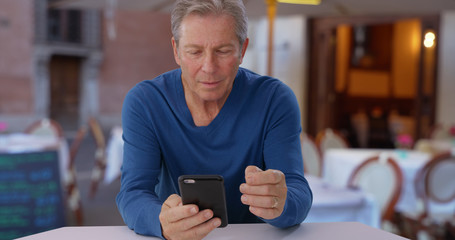 Caucasian male senior uses smartphone while sitting at restaurant in Europe