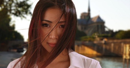 Close up of Asian woman in Paris looking at camera hair blowing in wind