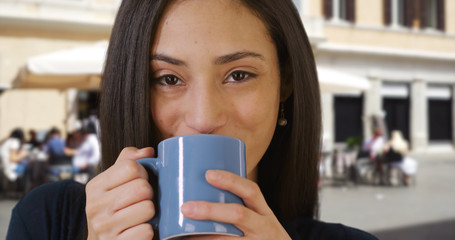 Closeup of pretty Latin woman enjoying cup of coffee outdoors in daytime