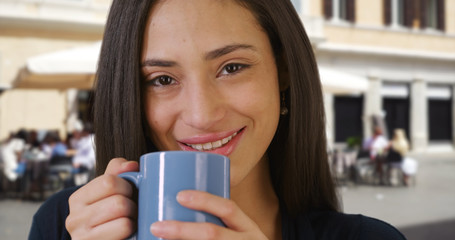 Close up of pretty Latin woman enjoying cup of coffee outdoors in daytime