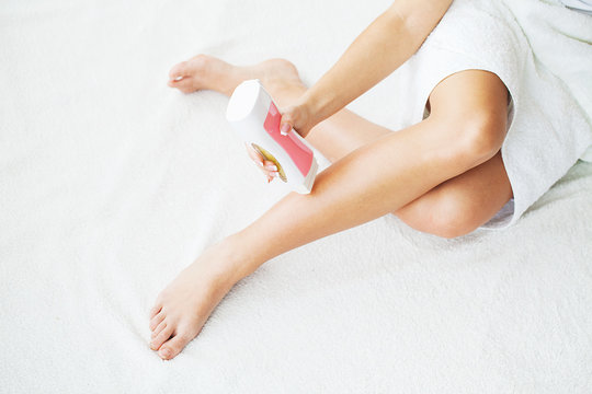 Skin Care and Health. Hair Removal. Fit Young Woman Waxing Her Legs With a Portable Roll-on Depilatory Wax Heater For Painless Hair Removal At Home