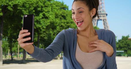 Beautiful Latin female takes selfie near Eiffel Tower in Paris France