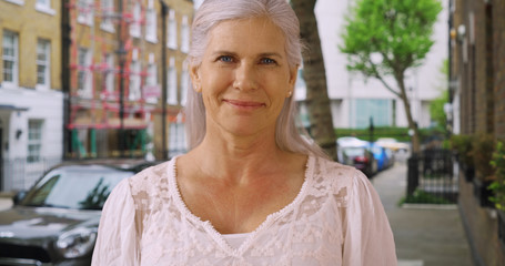 Casual portrait of lovely mature woman standing on residential street in London