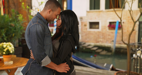 African boyfriend and girlfriend kiss passionately in Venice Italy