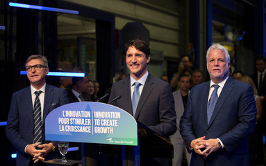 Canada's PM Trudeau answers questions from the media with Quebec Premier Couillard and CAE Inc. president and CEO Parent at CAE Inc., in Montreal, Quebec