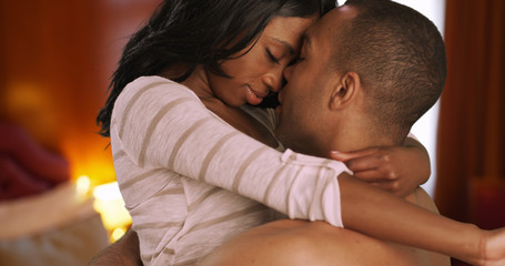 Romantic black male and female get sensual together in bedroom
