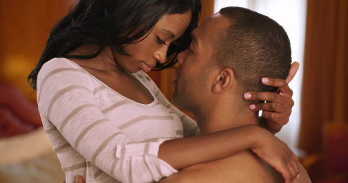 Intimate African couple showing affection privately in bedroom