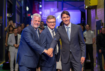 Canada's PM Trudeau poses with Quebec Premier Couillard and CAE Inc. president and CEO Parent after a news conference at CAE Inc., in Montreal, Quebec