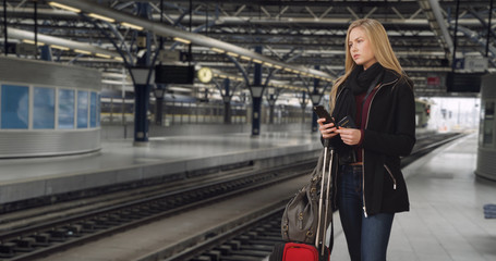 Traveling young white female waits for train to arrive at station