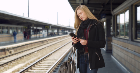 Caucasian female tourist searches train schedule while waiting at train station