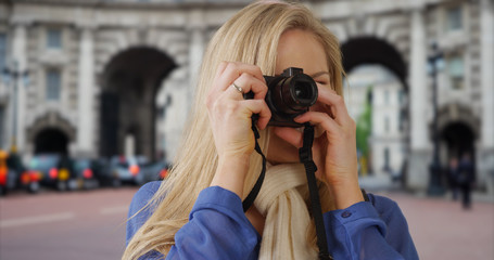 Traveling young white woman takes pictures near Admiralty Arch in London