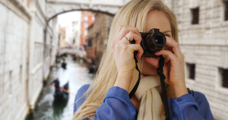 Beautiful Caucasian tourist with digital camera taking photos around Venice