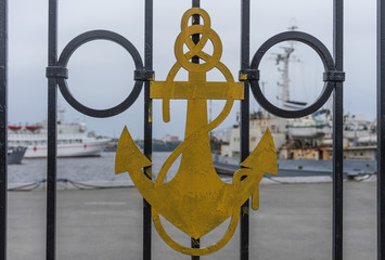 Naval symbols on the metal railing of the dock warships.