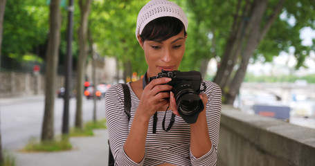 Portrait of black photographer taking photos outside in city setting