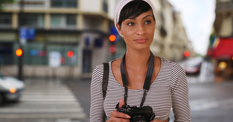 Young African woman shooting photographs in the city