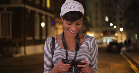 black woman looks over photos while out shooting in the city at night