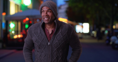 African-American man in winter clothing standing outside on cold evening