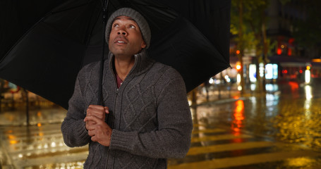 African male holding umbrella outside on rainy night in the city