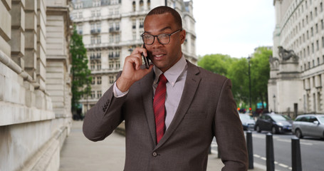 Modern African-American businessman in London chatting with client on phone