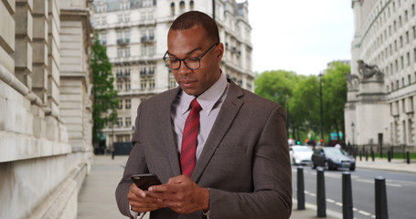 Modern African-American businessman in London sending texts with phone