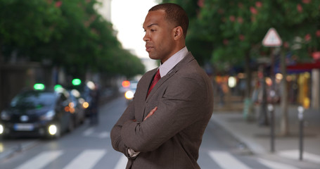 Aspiring African-American professional in city street with arms crossed