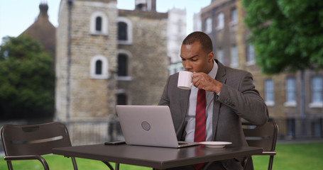 Hard-working black professional drinking coffee and using laptop in park