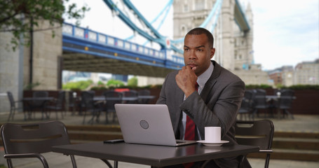 African businessman working on laptop while drinking coffee at London cafe