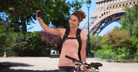 Caucasian brunette on bike ride in Paris stops to take selfie near Eiffel Tower