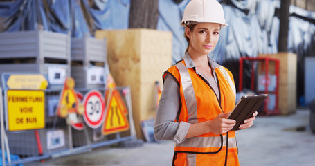 Confident woman contractor posing confidently with tablet on construction site