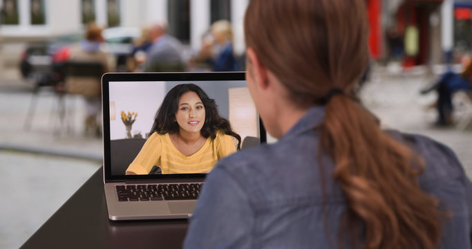 Millennial brunette video chatting with Hispanic friend on her computer at cafe