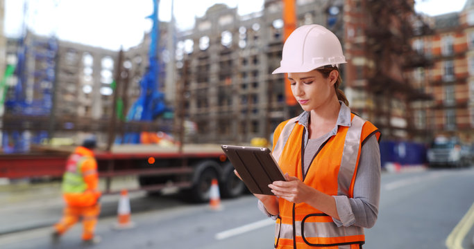 Hardworking Caucasian female construction worker looking over blueprints on pad