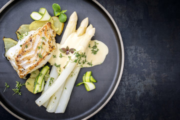 Modern style German fried cod fish filet with white asparagus in hollandaise sauce with roast potatoes and sliced zucchini as top view on a plate with copy space right
