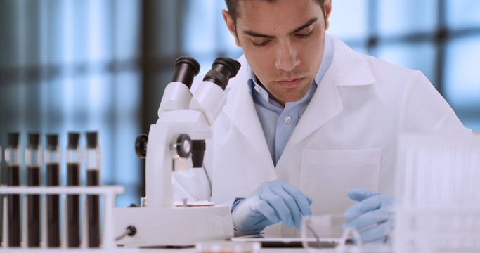 Young Hispanic forensic scientist looking at blood sample through microscope