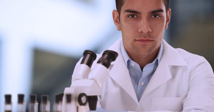 Portrait of attractive Hispanic male scientist inside laboratory