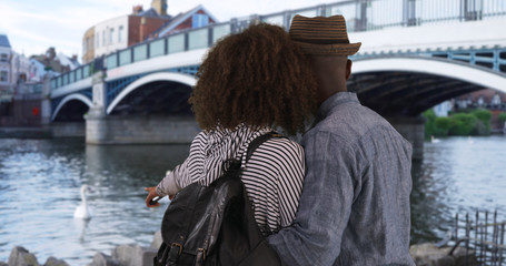 Happy millennial couple stand near Eton bridge Windsor looking at the water