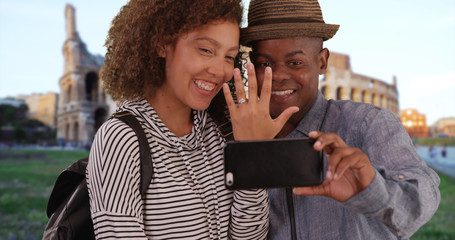 Happy engaged couple take picture with smartphone in front of Coliseum