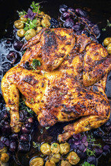 Modern spatchcocked barbecue chicken al mattone chili with red and green grapes as top view on an old metal sheet